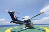 stock photo of offshoring  - helicopter parking landing on offshore platform. Helicopter transfer crews or passenger to work in offshore oil and gas industry. ** Note: Soft Focus at 100%, best at smaller sizes - JPG