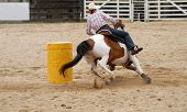 foto of barrel racing  - cow girl rounding the barrel at the rodeo - JPG