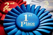 image of rosettes  - 1st place blue winners rosette or badge to be awarded as a prize to the winner of a competition made of pleated blue ribbon with central text in gold with a 2nd place red rosette behind - JPG