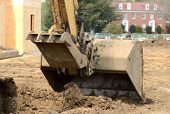 stock photo of track-hoe  - Small track hoe excavator to digging a water line trench on a new commercial residential development