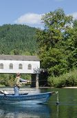 picture of mckenzie  - A fisherman in a drift boat casts his line just below the Goodpasture covered bridge on the Mckenzie River near Eugene Oregon - JPG