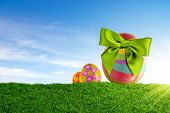 image of easter-eggs  - Three colorful Easter eggs with green bow on a grass field - JPG