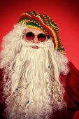 stock photo of hippy  - Portrait of a casual Santa Claus hippie over festive red background - JPG
