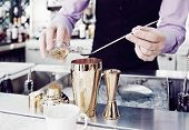 stock photo of bartender  - Bartender is adding ingredient in shaker at bar counter - JPG
