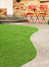 stock photo of grass area  - Walk way with perfect grass landscaping with artificial grass in residential area - JPG