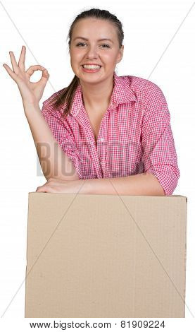 Woman leaning on cardboard box, making okay gesture