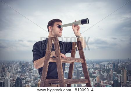 Young businessman looking for future opportunities through the spyglass standing on stairs.  Cloudy