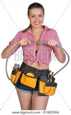 Woman in tool belt holding flexible tap hose