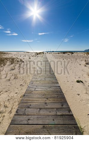 Wooden Walkway Leading To The Beach Over Sand Dunes