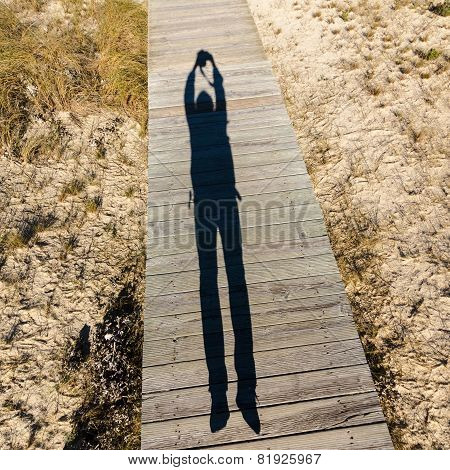 Elongated Shadow Jumping Man On A Wooden Walkway