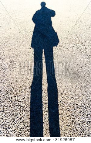 Elongated Shadow Of A Person Standing On The Road