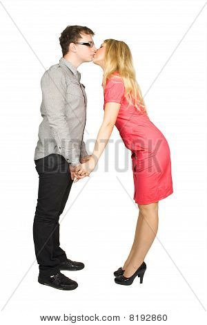 Young Man In Glasses And Blond Girl In Red Dress Standing And Kissing Isolated On White, Side View