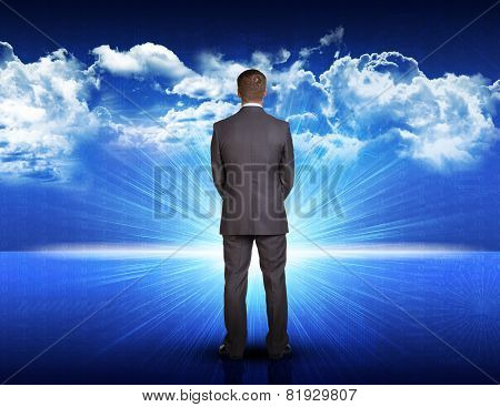 Businessman standing against blue landscape with rising sun
