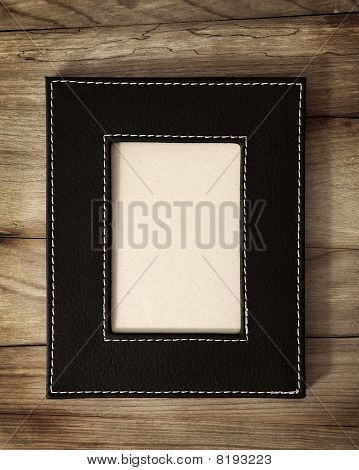 Leather frame on wooden background