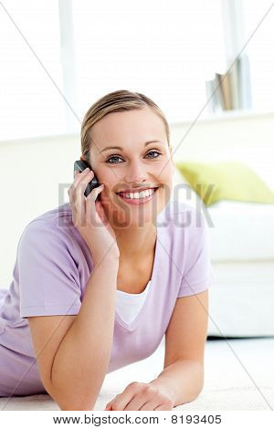 Attractive Woman Talking On Phone Lying On The Floor
