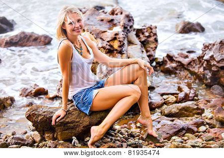 Beautiful Young Blonde Woman Posing Outdoor At The Rocky Sea Shore