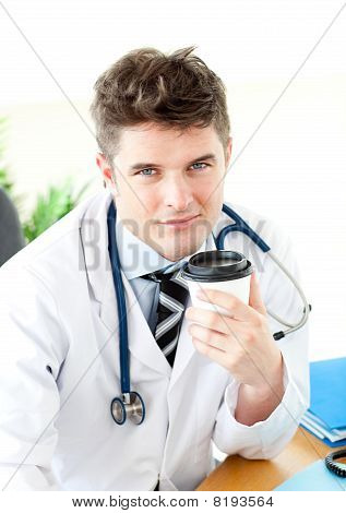 Serious male doctor drinking coffee
