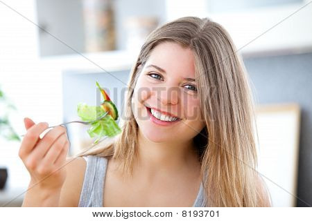 Bright woman eating a salad smiling at the camera