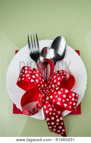 Valentines day table setting with plate, fork, red ribbon and hearts