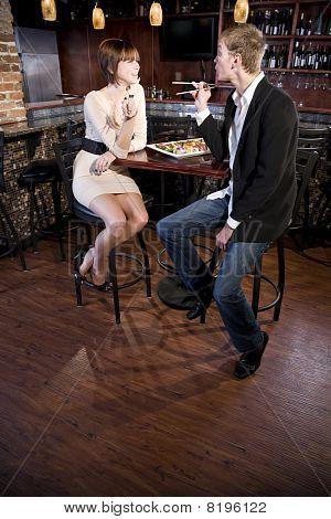 Couple Eating Sushi In Japanese Restaurant Talking