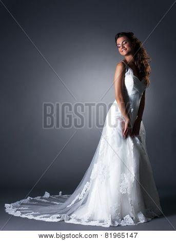 Happy bride posing in elegant wedding dress