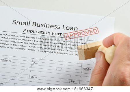 Person Hand Holding Rubber Stamp Over Loan Application