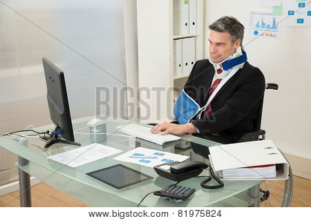 Disabled Businessman On Wheelchair Using Computer
