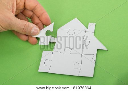 Person Solving House Jigsaw Puzzle
