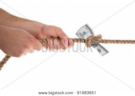 Person Pulling Banknote Tied In A Rope