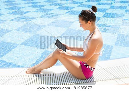 Woman Using Digital Tablet At The Edge Of Swimming Pool