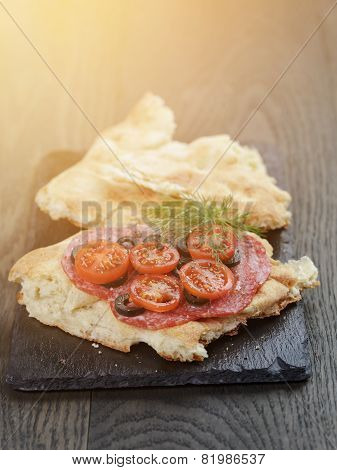 flat pita bread with salami and vegetables on slate board