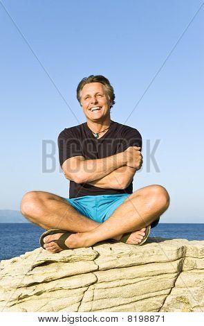 happy man sitting on rock.