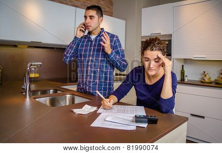 Angry man arguing at phone while woman calculating credit lines
