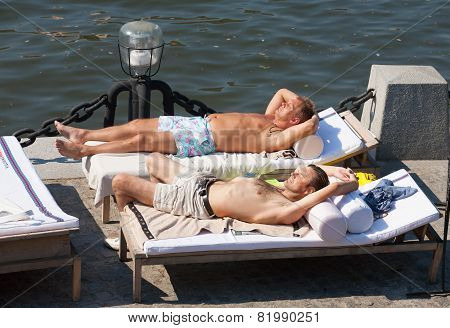 Two Man Lying On Couches And Sunbathing At Olive Beach