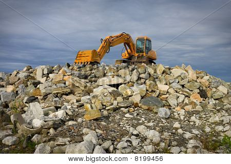 Excavator On  Heap Of Stones