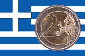 foto of common  - Common face of two euros coin isolated on the national flag of Greece as background - JPG