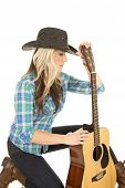 picture of cowgirl  - A cowgirl kneeling holding onto her guitar - JPG