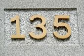 picture of numbers counting  - Image of the number 135 on a wall indicating a house number - JPG