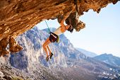 image of cliffs  - Young female rock climber on a face of cliff - JPG