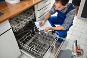 picture of dishwasher  - Male Technician Sitting Near Dishwasher Writing On Clipboard In Kitchen - JPG