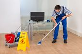 picture of janitor  - Portrait Of A Male Janitor Cleaning Office With Wet Floor Sign - JPG