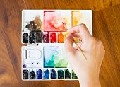 picture of paint palette  - Paintbrush and paint palette with artist - JPG