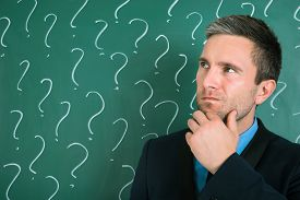 image of thoughtfulness  - Thoughtful Businessman In Front Of Chalkboard With Question Mark Sign - JPG