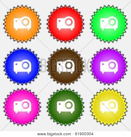 Projector  Icon Sign. A Set Of Nine Different Colored Labels. Vector