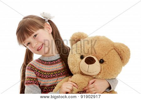 Charming girl with tails hugging a Teddy bear