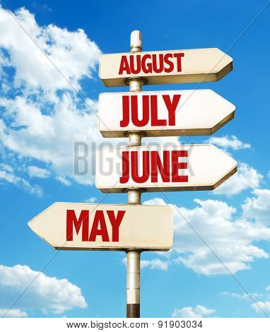 June/July/August direction sign with sky background