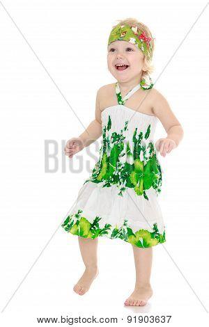 Very little girl in a green summer dress barefoot