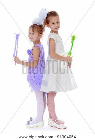 two well-dressed girl holding a magic wand
