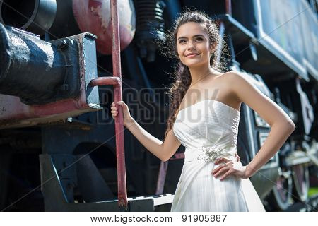 Portrait of happy wedding bride near the old steam locomotiv