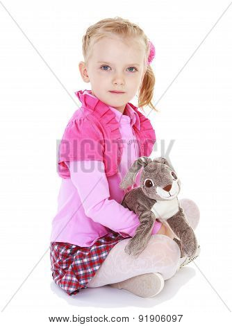 Pretty serious girl sitting on the floor and holding a toy rabbi